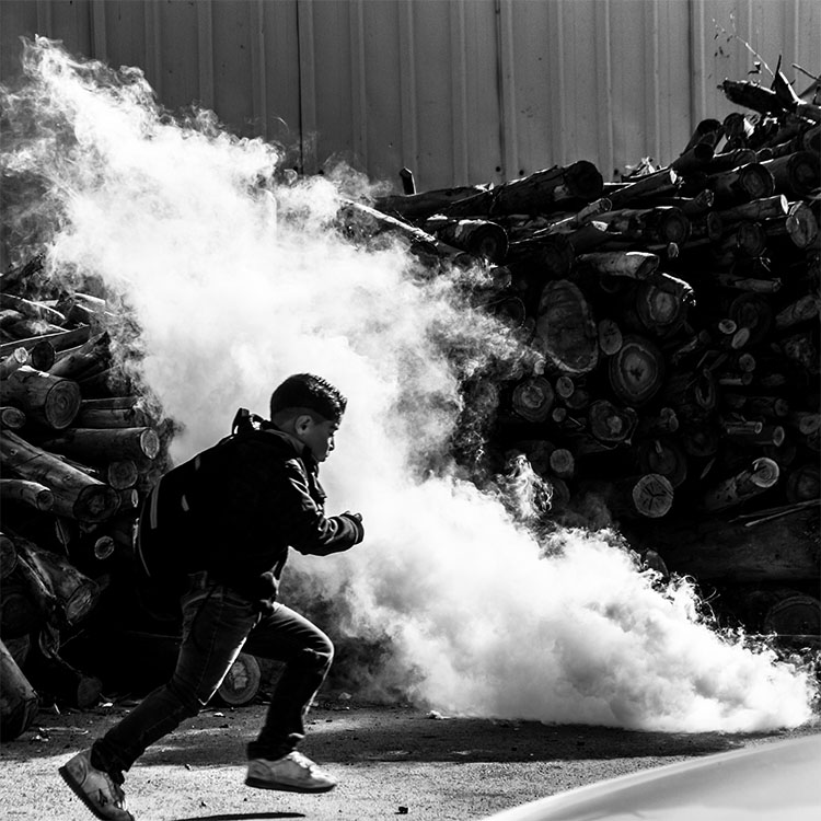 A Palestinian boy tries to evade an onslaught of Israeli tear gas on his way to school.